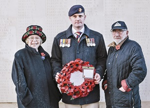Liam Young poses with his fellow members and holds a poppy wreath