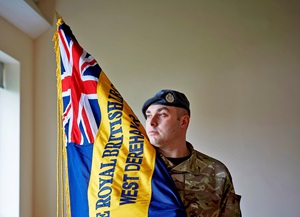 Tom Foy in battledress holds his branch Standard