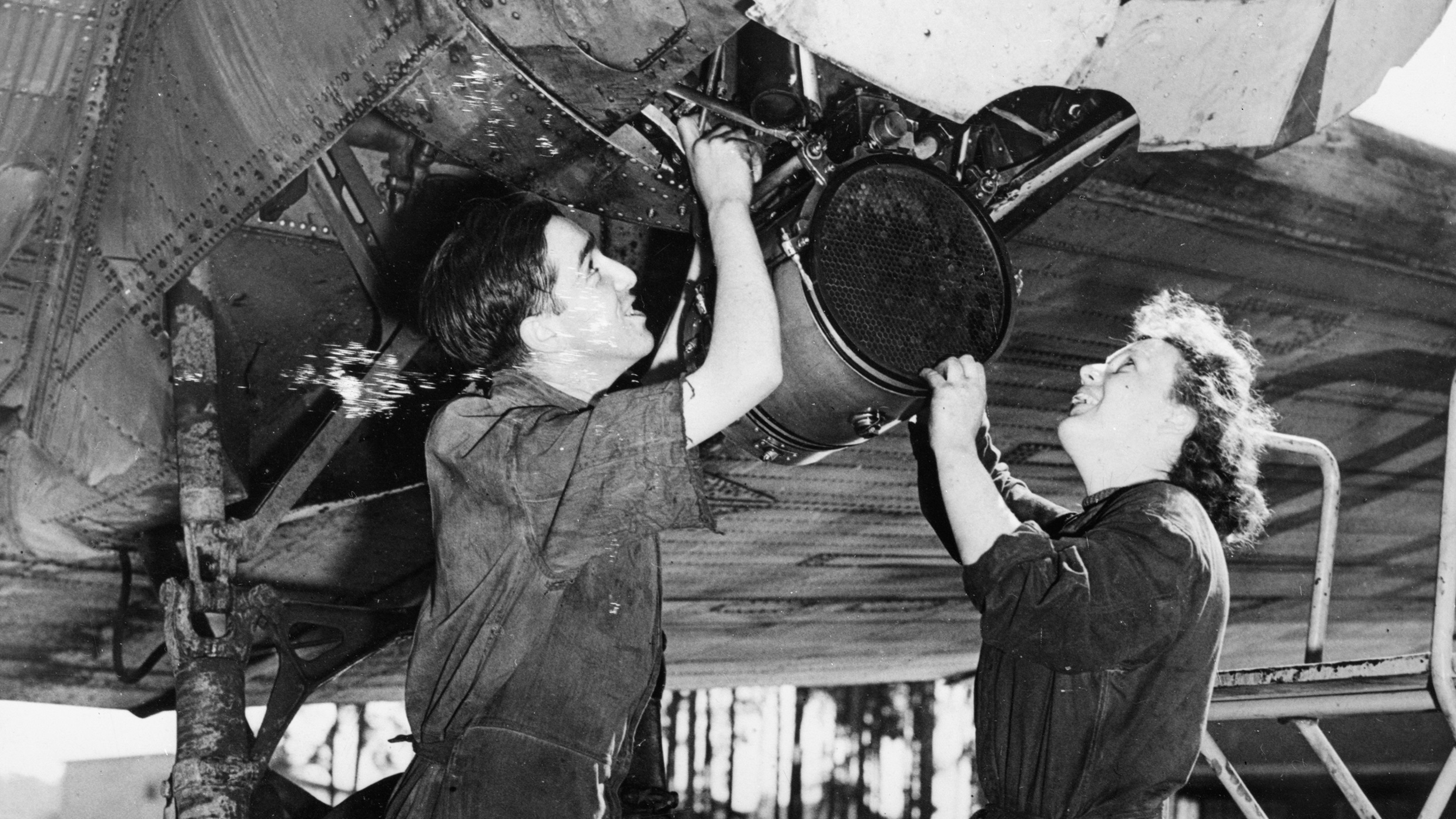 RAF and WRAF fitters working on the engine of an aircraft at Gatow. The WRAF fitter, Corporal Fisher, thought nothing of working 16 hours if necessary and was decorated for her outstanding service.