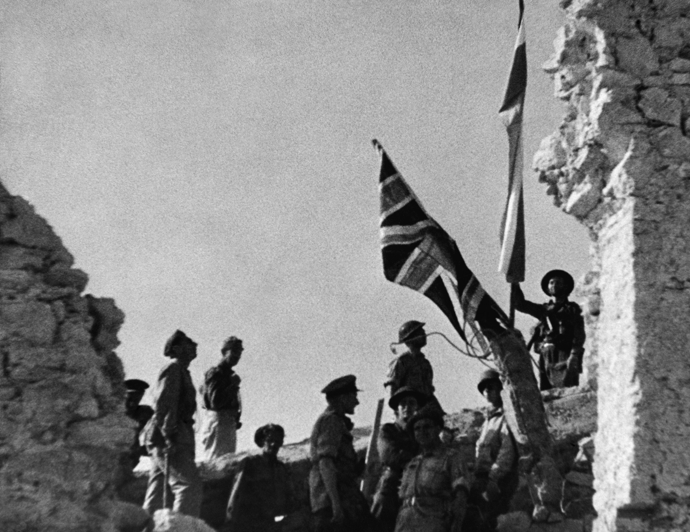 British and Polish troops (3rd Carpathian Rifles Division, 2nd Corps) raising the Union Jack alongside the Polish flag in the ruins of the Monte Cassino Monastery, 18 May 1944.