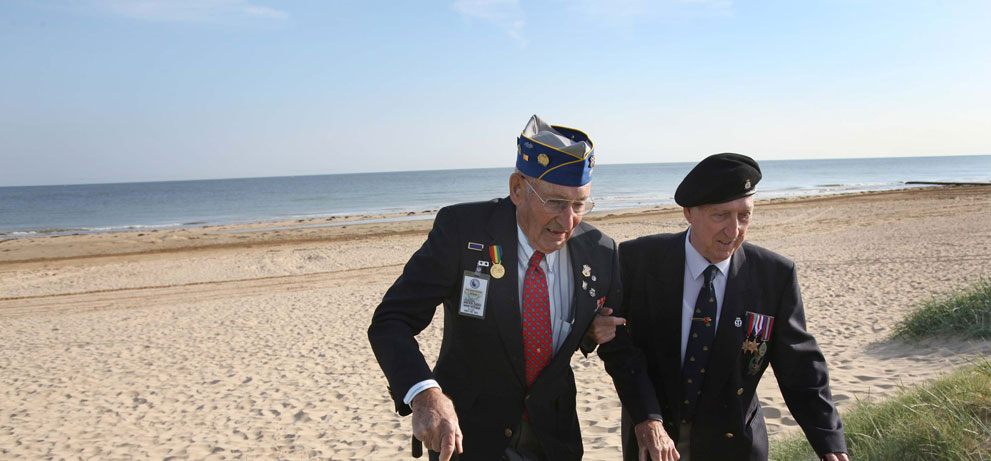 WW2 D-Day veterans walking on D-Day landing beaches wearing their medals.