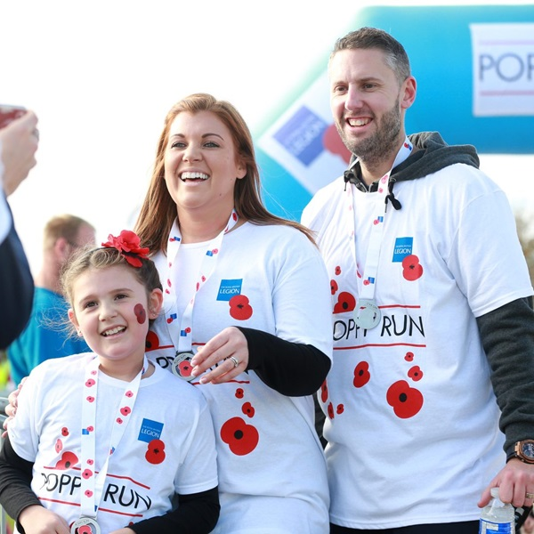 Poppy Run Manchester participants wearing their medals and being photographed at the end of the race.