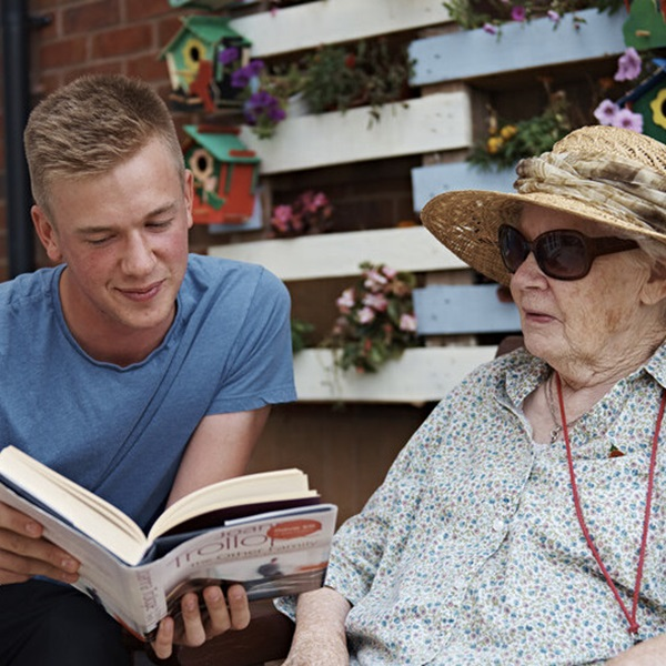A young volunteer reading to a member of the Armed Forces community